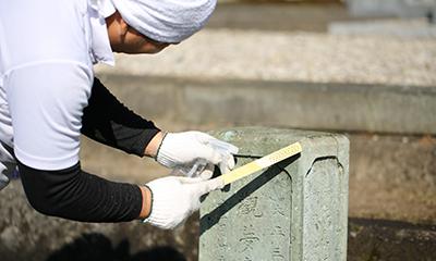墓石を清掃する男性