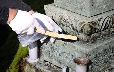 お墓の清掃をしている男性